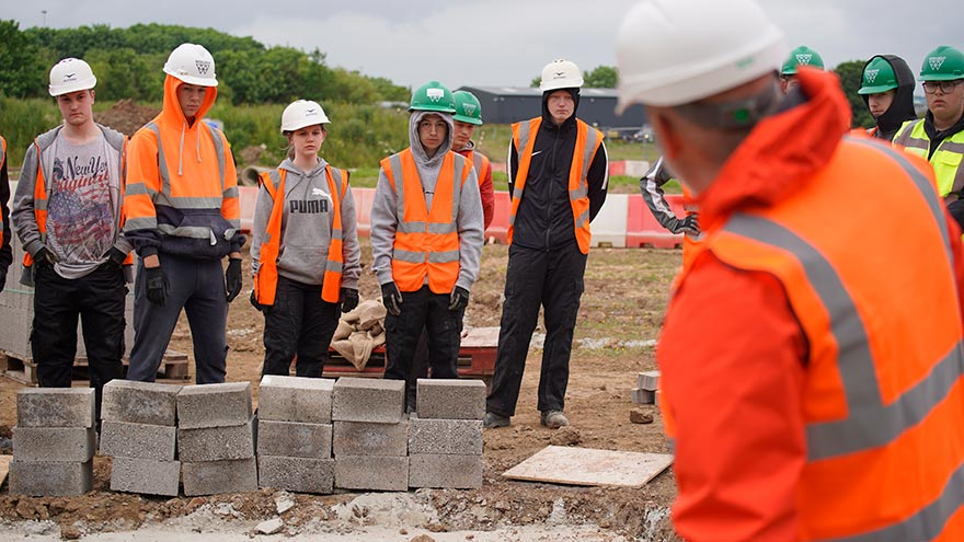 John Cartwright (Head of Construction and The Built Environment on site with bricklaying students