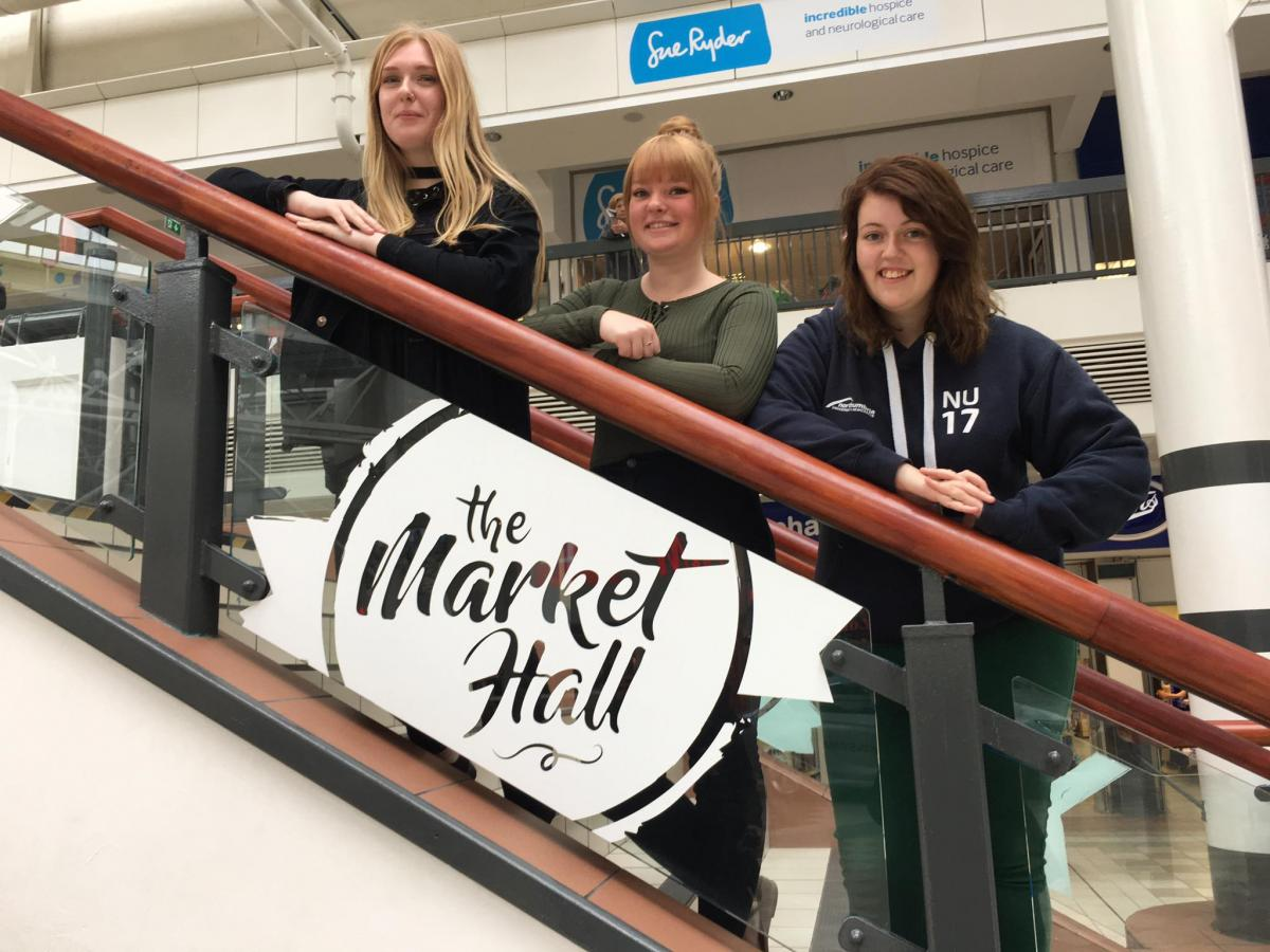 HCFE Creative students, from left to right, Ashleigh Humble, Robyn Hart and Danielle O'Neill with the Market Hall logo.